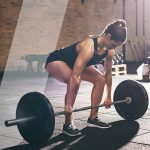 A woman squats down to pick up a barbell with weights to help her with strength training.