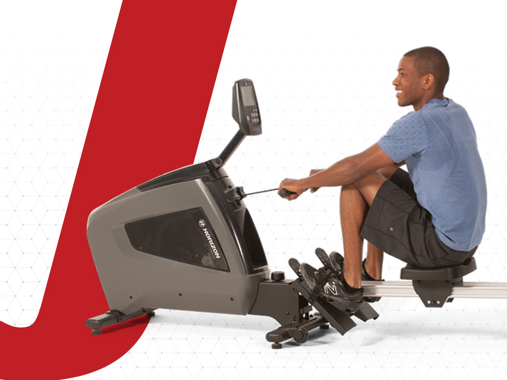 A man is indoor rowing on a rowing machine.