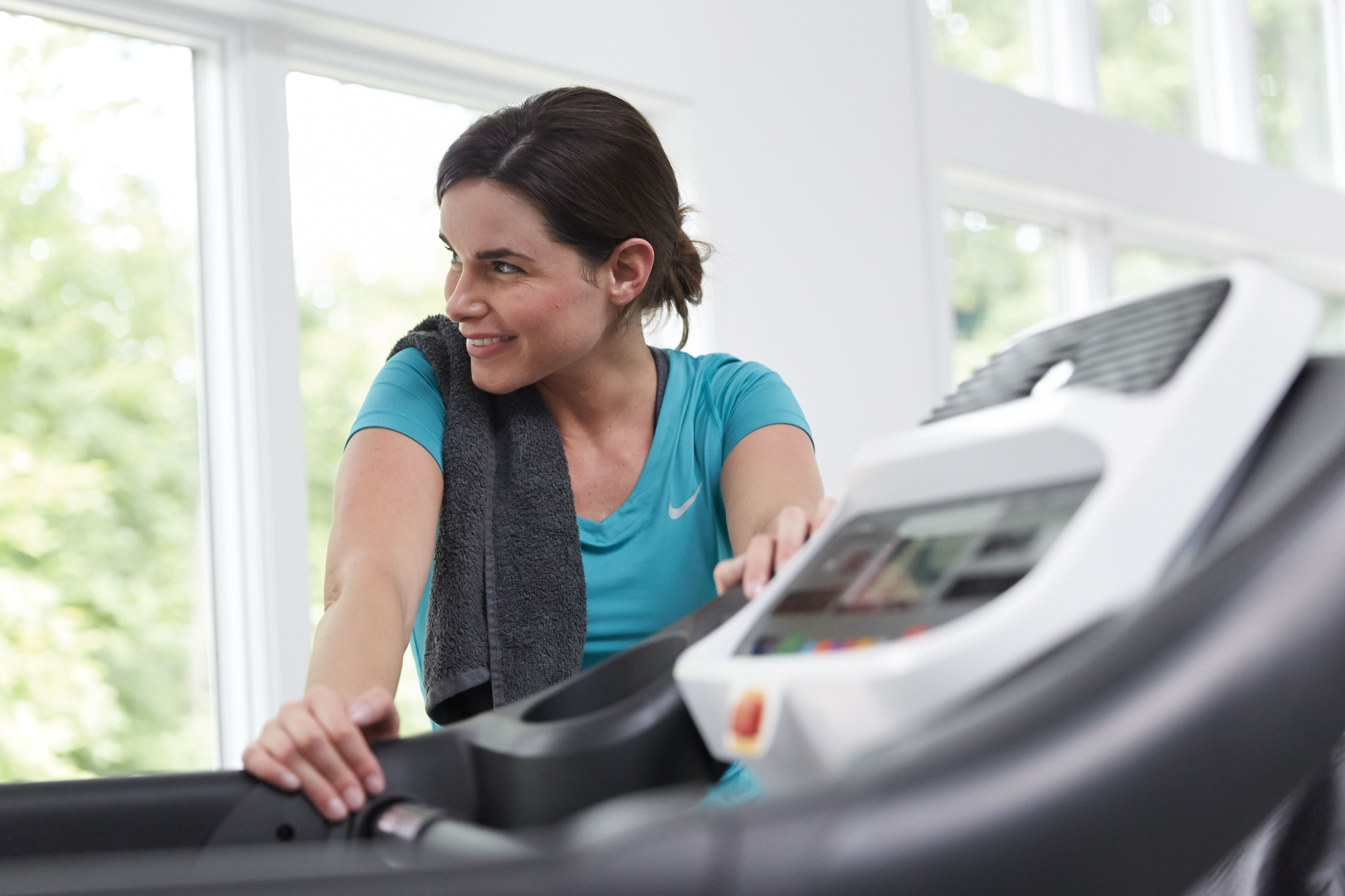 Woman holds onto a treadmill