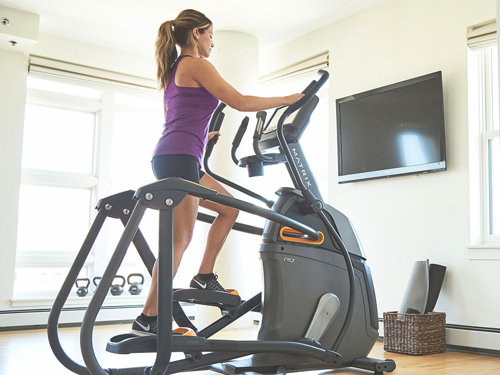 A woman is exercising and doing a HIIT elliptical workout.